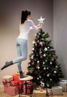 Vista frontal mulher decorando a árvore de natal
