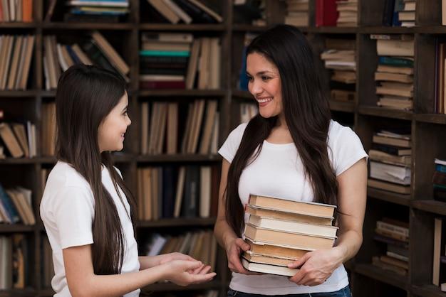 Vista frontal mulher e jovem garota juntos na biblioteca