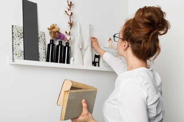 Vista frontal mulher em casa levando livros da prateleira