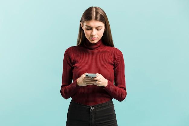 Vista frontal mulher em seu telefone