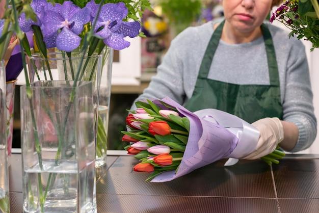 Vista frontal mulher embrulhando tulipas