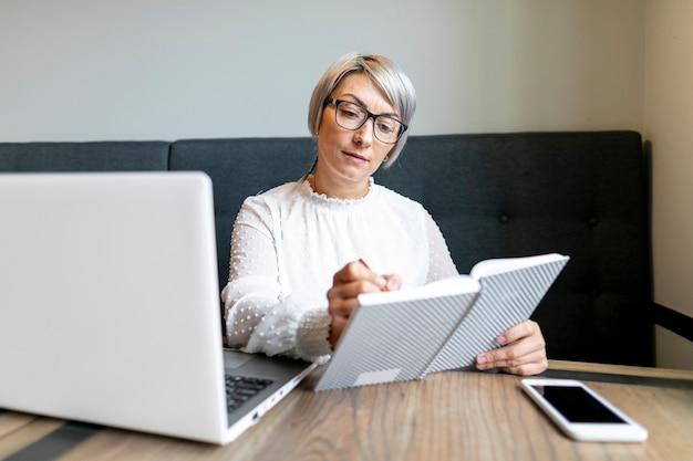 Vista frontal mulher escrevendo na agenda