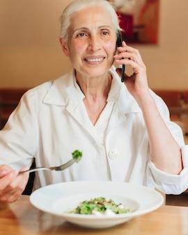 Vista frontal mulher falando ao telefone