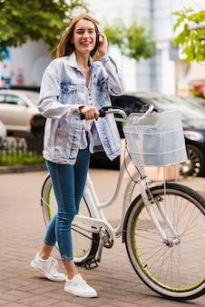 Vista frontal mulher feliz com sua bicicleta