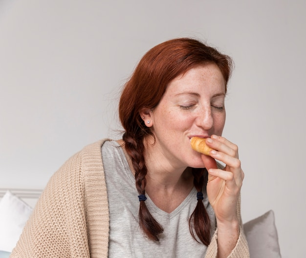 Vista frontal mulher grávida desfrutando croissant