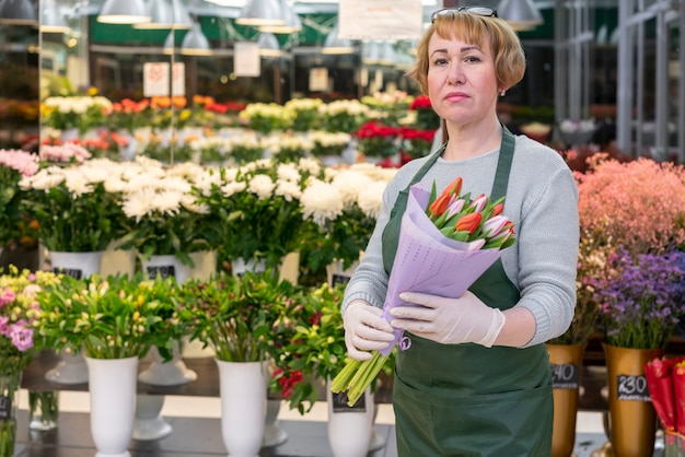 Vista frontal mulher idosa segurando tulipas