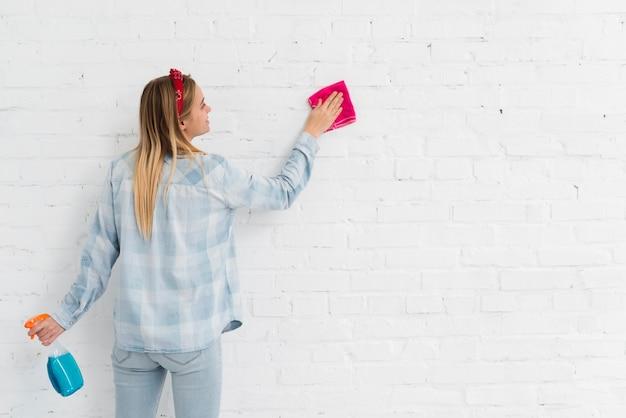 Vista frontal mulher limpando a parede