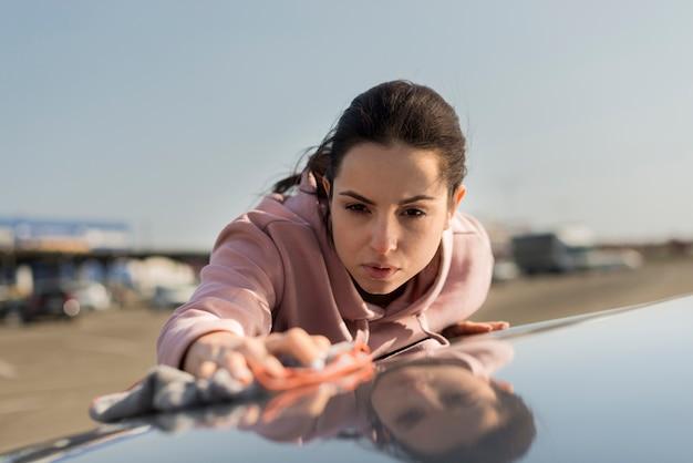 Vista frontal mulher limpando o capô do carro