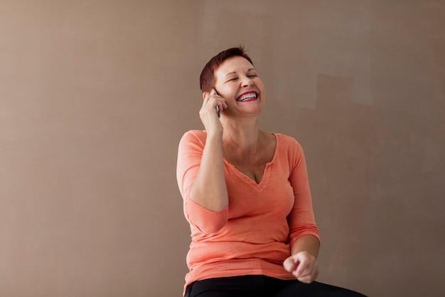 Vista frontal mulher madura falando ao telefone