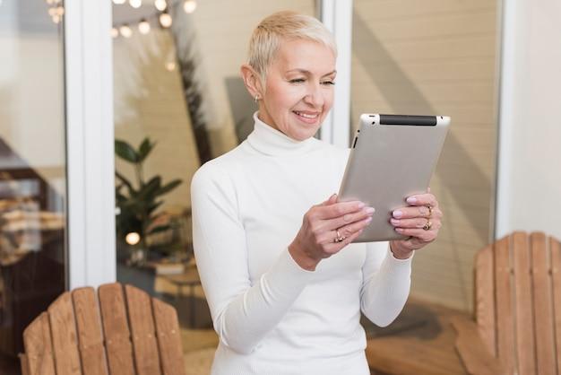 Vista frontal mulher madura olhando no seu tablet dentro de casa