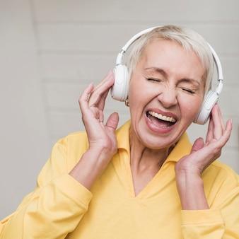 Vista frontal mulher madura ouvindo música
