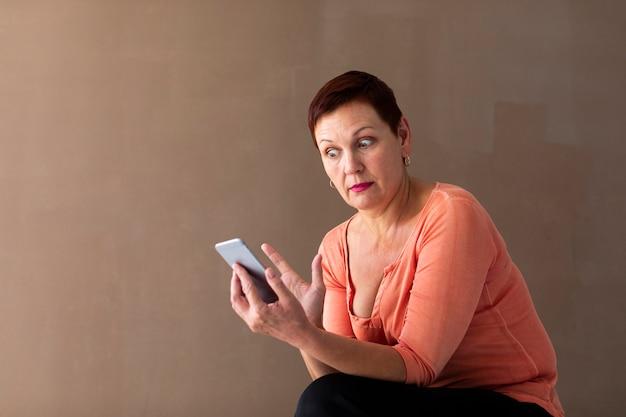Vista frontal mulher madura, segurando o telefone