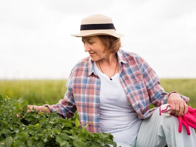 Vista frontal mulher mais velha, ficar ao lado de uma planta em seu jardim