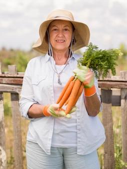 Vista frontal mulher mais velha, segurando algumas cenouras frescas na mão
