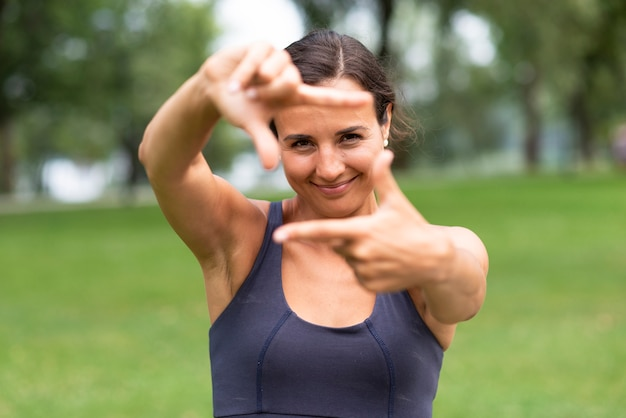 Vista frontal mulher mulher câmera gesto com a mão
