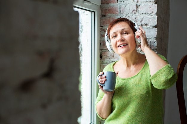 Vista frontal mulher na janela, ouvir música