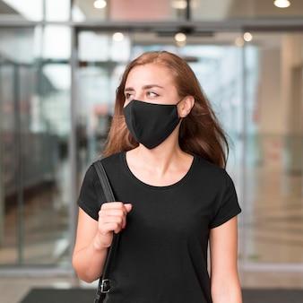 Vista frontal mulher no shopping vestindo máscara