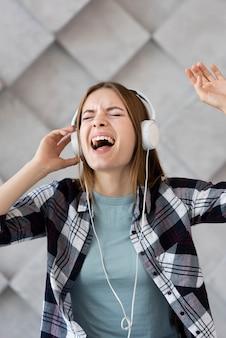 Vista frontal mulher ouvindo música em fones de ouvido