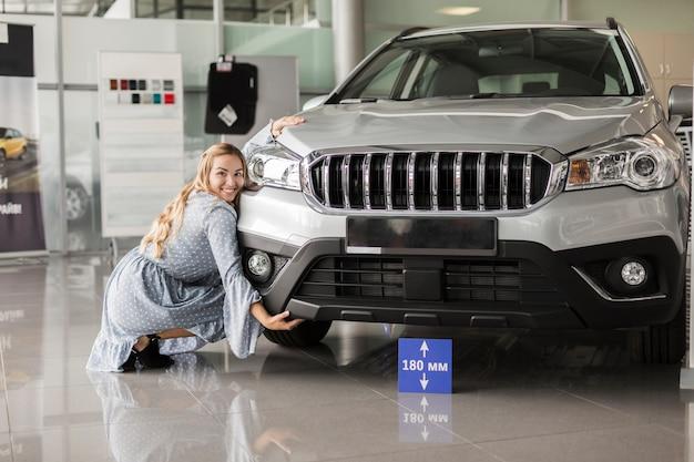 Vista frontal mulher posando ao lado de um carro