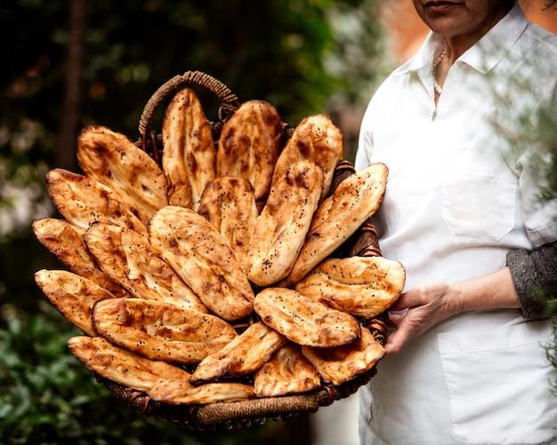 Vista frontal, mulher segura, cesta, com, pão tandoor