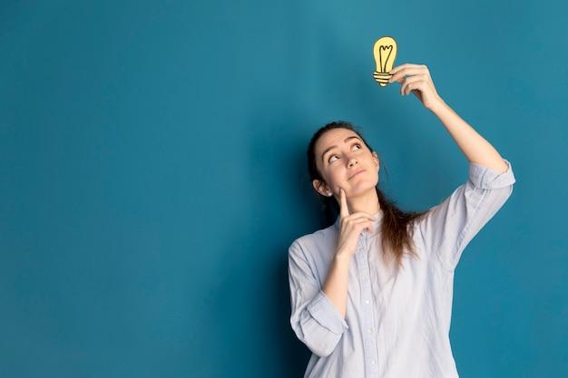 Vista frontal mulher segurando a ideia de luz