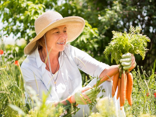 Vista frontal mulher segurando algumas cenouras frescas na mão