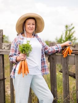 Vista frontal mulher segurando algumas cenouras na mão