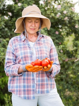 Vista frontal mulher segurando alguns tomates frescos na mão