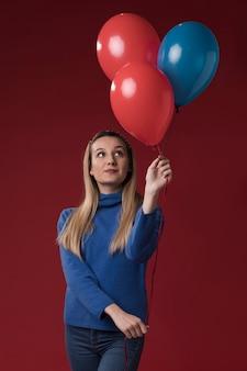 Vista frontal mulher segurando balões