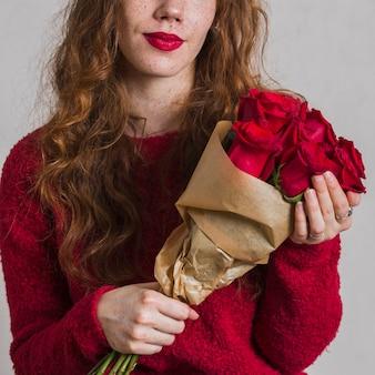 Vista frontal mulher segurando buquê de rosas