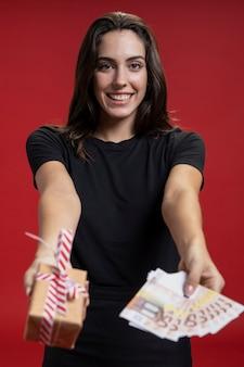 Vista frontal mulher segurando cartões de crédito e presente