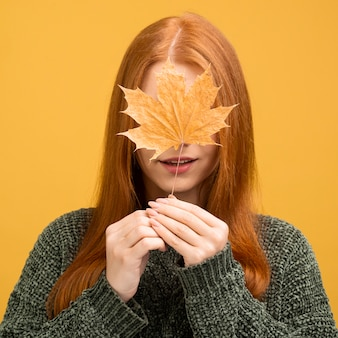 Vista frontal mulher segurando folha amarela