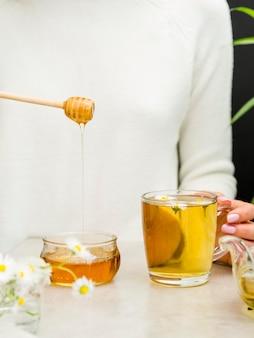 Vista frontal mulher segurando mel dipper e copo com chá