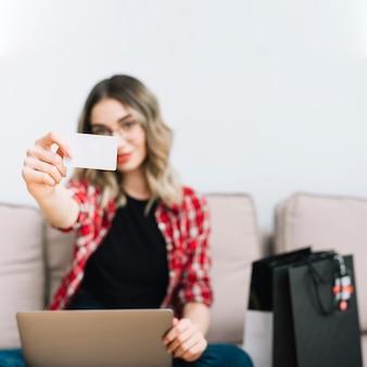 Vista frontal mulher segurando o cartão enquanto está sentado no sofá