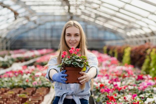 Vista frontal mulher segurando o vaso de flores