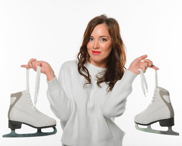 Vista frontal mulher segurando patins de gelo