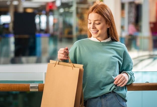 Vista frontal mulher segurando sacola de compras