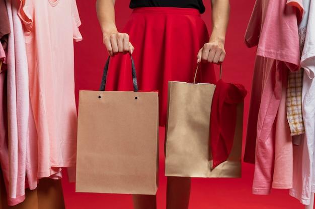 Vista frontal mulher segurando sacolas de compras