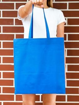 Vista frontal mulher segurando uma bolsa azul