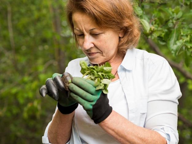 Vista frontal mulher segurando uma pequena planta nas mãos