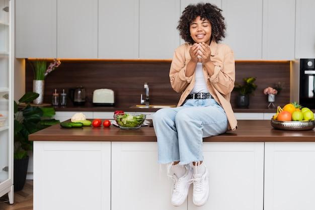 Vista frontal mulher segurando uma xícara de café na cozinha