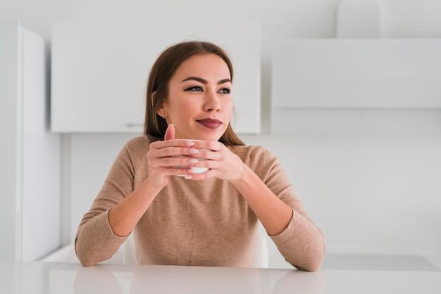 Vista frontal mulher segurando uma xícara de café