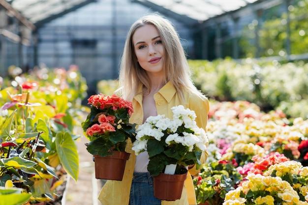 Vista frontal mulher segurando vasos com flores