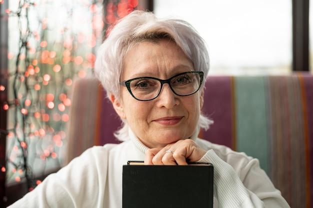 Vista frontal mulher sênior de óculos, segurando o livro