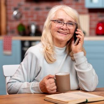 Vista frontal mulher sênior falando por telefone