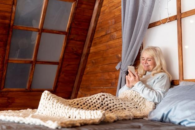 Vista frontal mulher sênior na cama com o celular