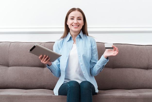 Vista frontal mulher sentada no sofá com tablet digital e cartão de crédito