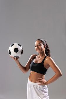 Vista frontal mulher sorridente com bola de futebol