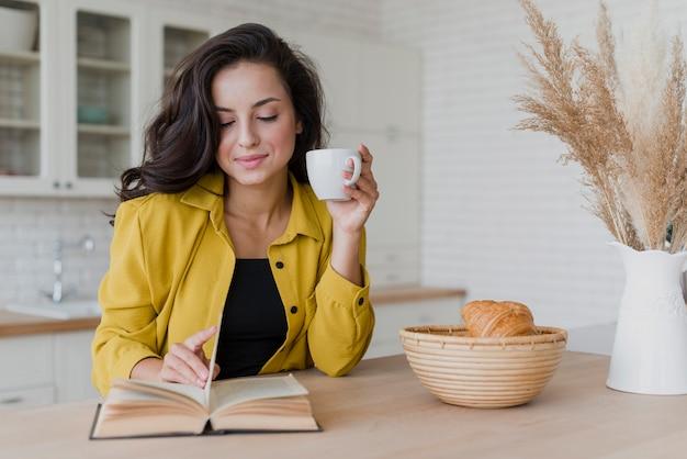 Vista frontal mulher sorridente com livro e xícara