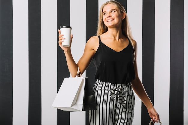 Vista frontal mulher sorridente com sacos de compras